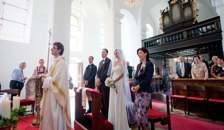 Hochzeitszeremonie mit Pfarrer, Brautpaar und Gästen in der Wallfahrtskirche Maria Hilf. (© www.mondsee.at)