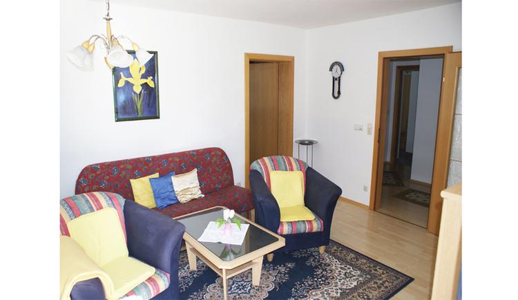 Wohnbereich mit Couch, Sesseln, Tisch, Teilweise Teppichboden