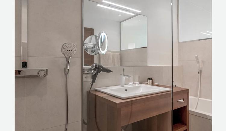 Badezimmer mit Dusche, Waschbecken, Unterschrank, Fön, Spiegel, Badewanne