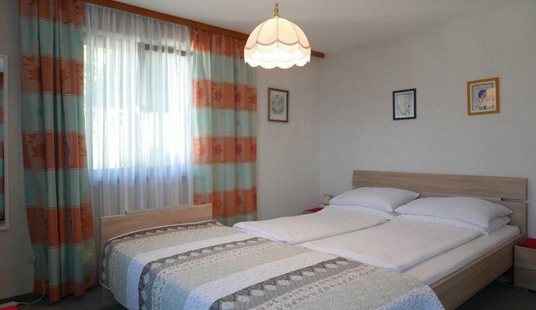 Schlafzimmer mit Doppelbett, davor ein Einzelbett, Nachtkästchen, seitlich ein Fenster