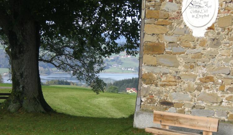 Holzbank vor einer Kapelle, zwischen der Kapelle und einem Baum sieht man zum See. (© www.mondsee.at)