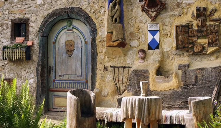 Eingangsbereich des alten Heimathauses am Irrsee mit Stühlen und Tisch neben der Tür.