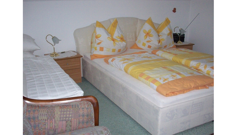 Bedroom with large bed, nightstand, table lamp, on the side a single bed