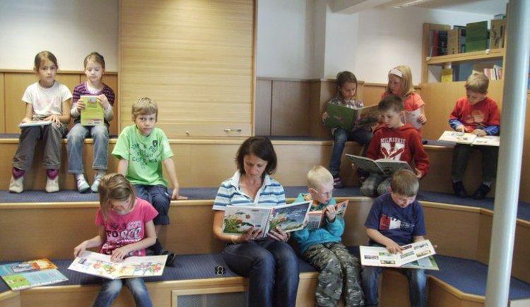 Leseraten beim Durchstöbern der Bücher (© Öffentliche Bücherei Faistenau)