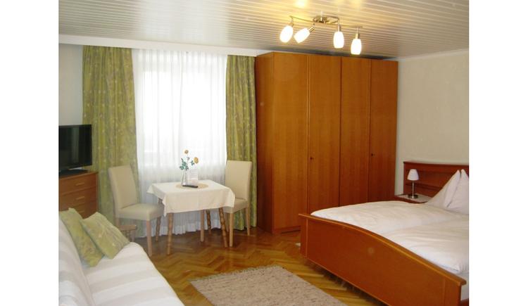 Doppelbett mit Nachtkästchen und Tischlampe, Kleiderschrank und ein Fenster im Hintergrund, Tisch mit Stühlen, Fernseher auf einer Kommode, im Vordergrund seitlich eine Ausziehcouch