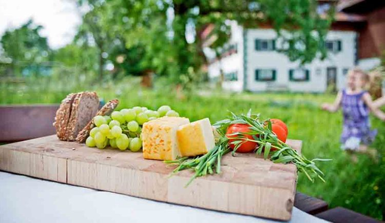 Cheese, bread, tomatoes and grapes on a wooden board, in the background the landscape. (© Gaderer)