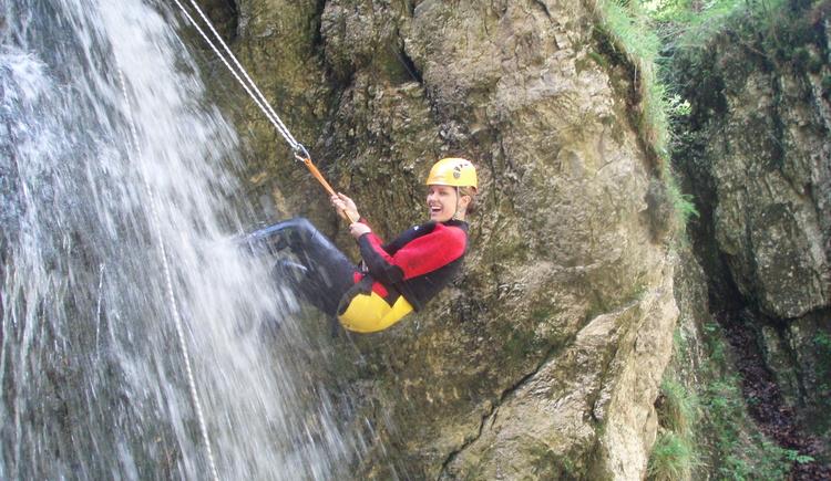 Dame am Klettersteig mit Wasserfall. (© Pyhrn-Priel)