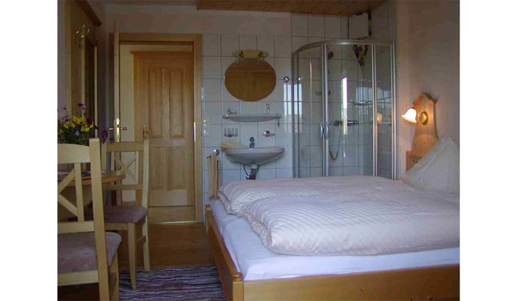 Double bed, side table with chairs, in the background a sink and a shower
