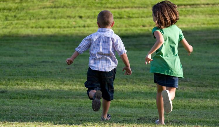 Kinder laufen in der Wiese