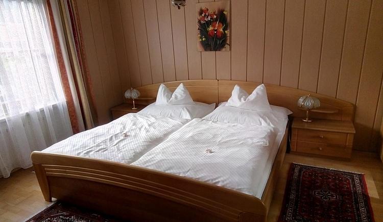 Freundliches Schlafzimmer der Ferienwohnung Kalmbergblick mit Doppelbett und Einbauschrank und Sitzgelegenheit. (© Gerlinde Sams)