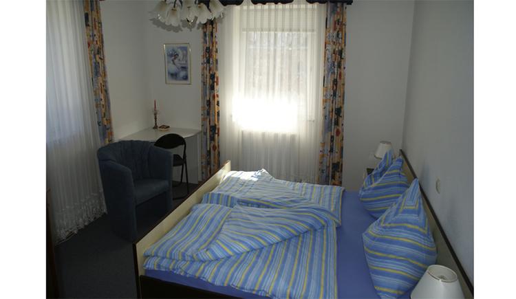 Schlafzimmer mit Doppelbett, Sessel und kleiner Tisch im Eck, im Hintergrund Fenster