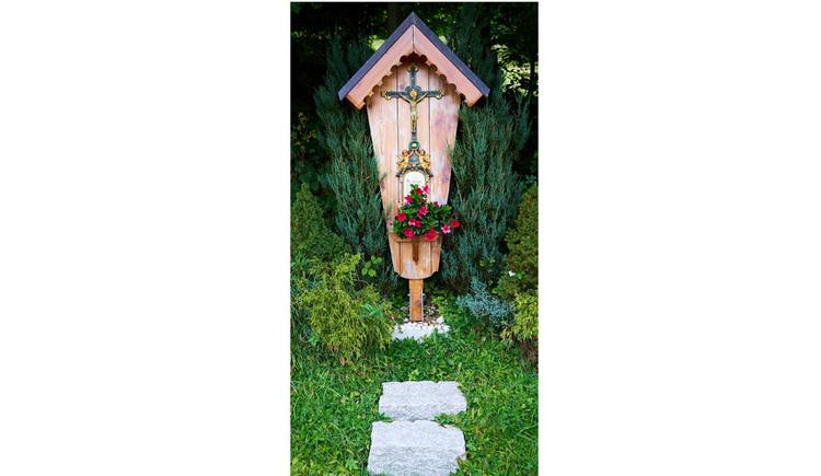 Blick auf das Holzkreuz, im Hintergrund Sträucher