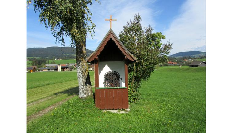 Blick auf die Kapelle in einer Wiese, seitlich Bäume