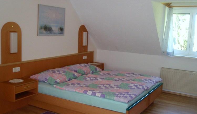 Das geräumige Schlafzimmer ist hell eingerichtet mit einem Doppelbett und Kleiderschrank