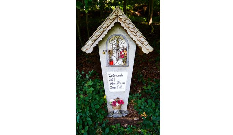 Blick auf den Bildstock, hinter Gitter eine Heiligenfigur, Blumen, Kerze, im Hintergrund Bäume