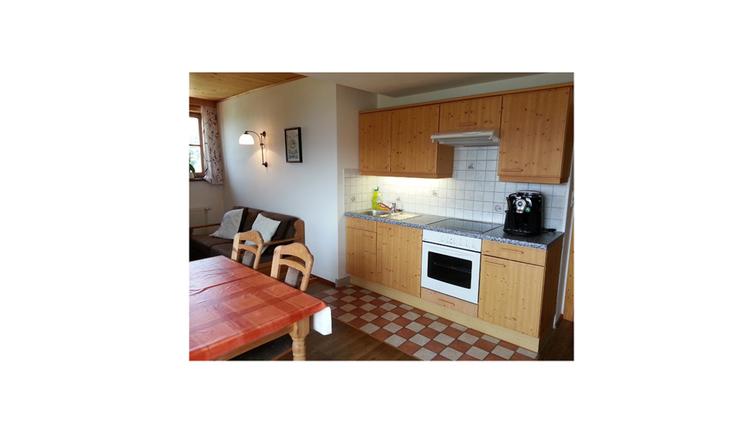 im Vordergrund Tisch und Stühle, im Hintergrund kleine Couch, seitlich die Küche, Herd, Kaffeeautomat