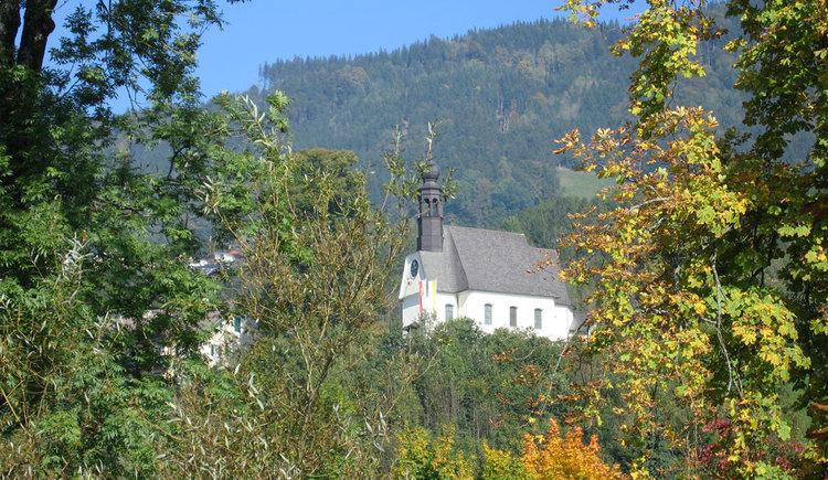 Blick auf die Hilfbergkirche inmitten von Bäumen in herbstlichen Farben. (© www.mondsee.at)