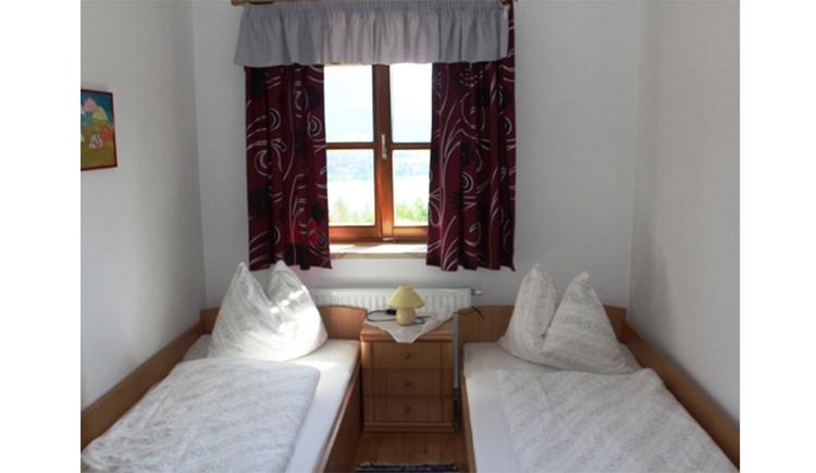 Schlafzimmer mit Einzelbetten, Nachtkästchen, Tischlampe, im Hintergrund ein Fenster