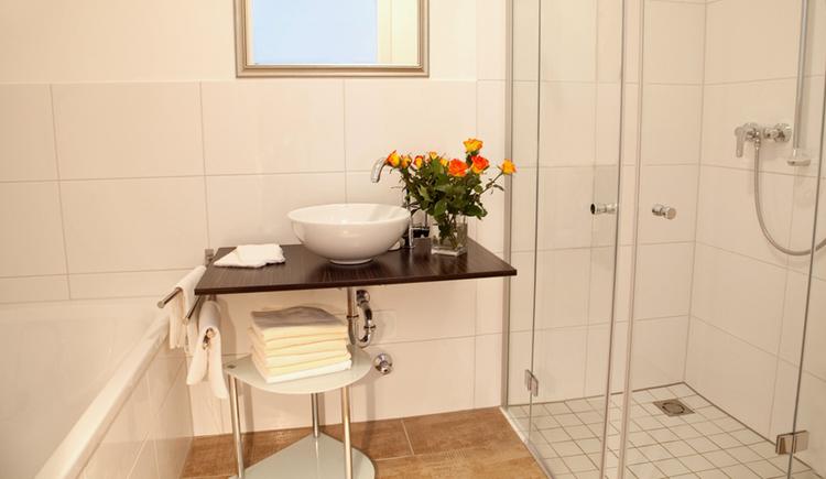 Badezimmer mit Badewanne, Dusche, im Hintergrund Waschbecken, daneben steht eine Vase mit Blumen, Spiegel
