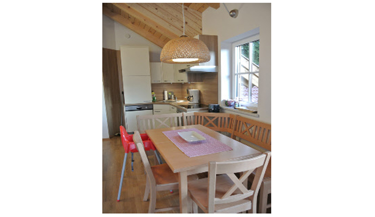 Dining area with Corner bench, table, chairs, high chair, kitchen in the background, window on the side