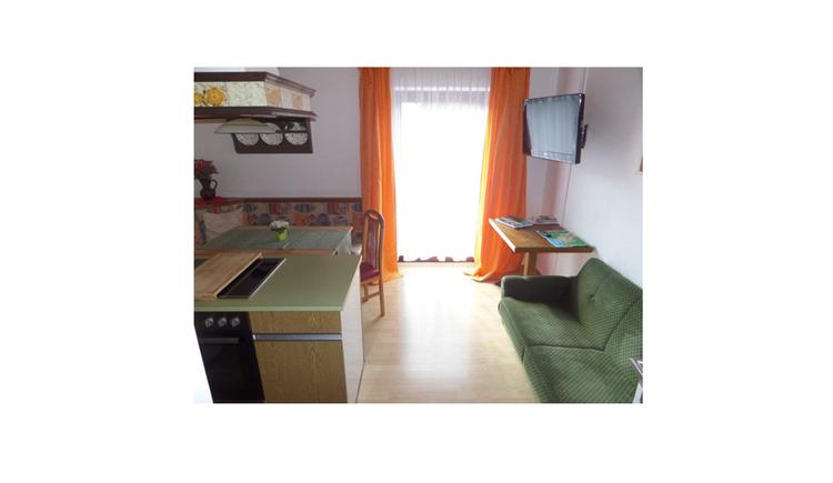 Wohnbereich, seitlich ein kleiner Teil von der Küche zu sehen, im Hintergrund Essbereich mit Eckbank, Tisch und Stuhl, Balkontür, an der Wand ein Fernseher montiert, kleiner Tisch darunter, Couch
