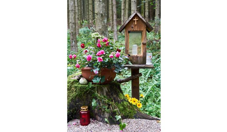 Blick auf ein Holzmarterl, seitlich Blumen und Kerzen, im Hintergrund ein Wald
