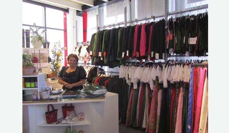 Person im Geschäft, seiltich hängt Kleidung an den Stangen