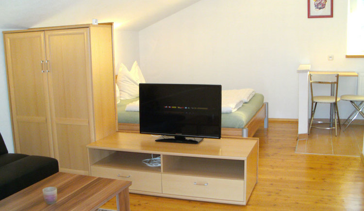 In the background double bed, table, chair, in the front a wardrobe, TV, couch and table