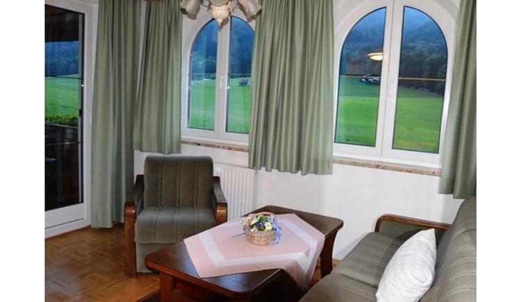 Wohnbereich mit Couch, Tisch und Sessel, im Hintergrund Fenster