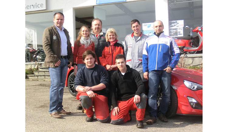 Team: workers in front of a car