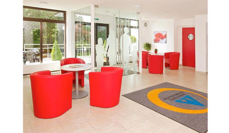 Eingangsbereich mit Tischen und Loungesesseln
