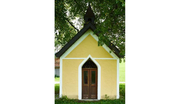 Blick auf die Kapelle mit Holztür, Baum im Hintergrund
