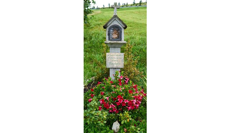Blick auf den Bildstock, im Vordergrund Blumen, im Hintergrund Wiesen