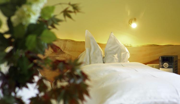 Doppelbett mit weißer Bettwäsche und Betthaupt aus ungeradem Holzbrett