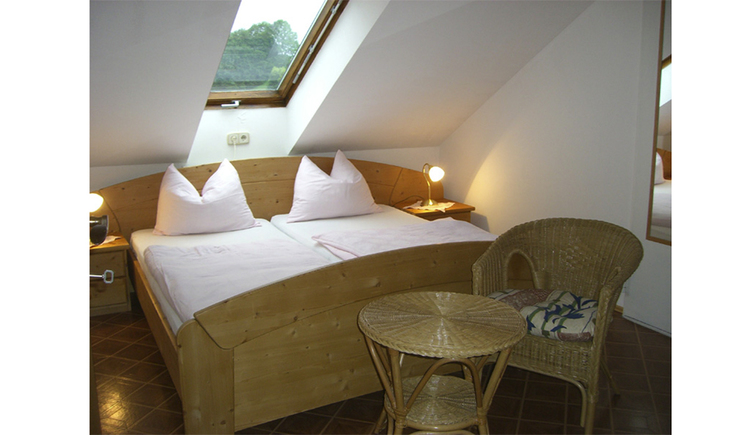 double bedroom with skylight and wickerchair