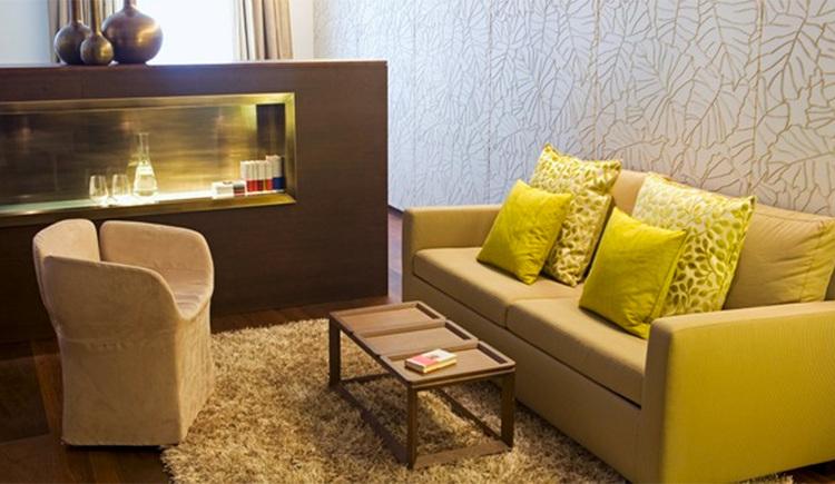 Blick in den Wohnbereich mit Sofa, Tisch und Sessel, im Hintergrund eine Kommode
