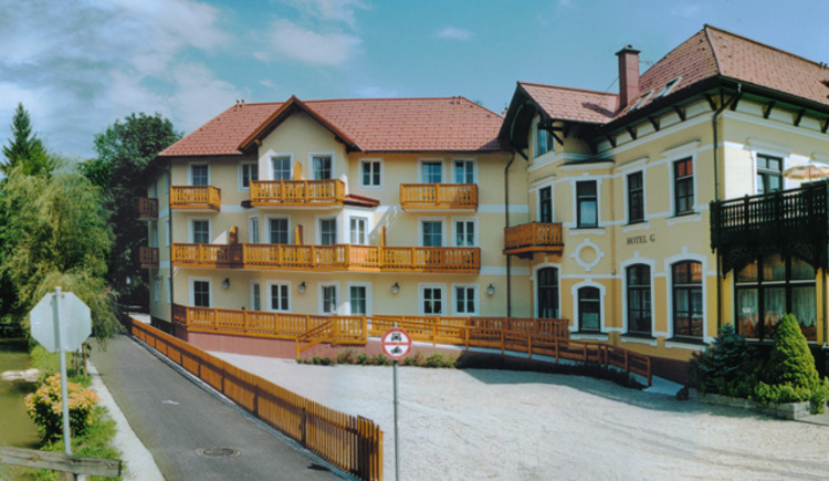 Exterior view of the Hotel Goisererhof in Bad Goisern. On the left side you will see the hotel-extention, in the front view the parking area. Divided by a fence there will be a small promenade, which is situated directly in front of the river Mühlbach.