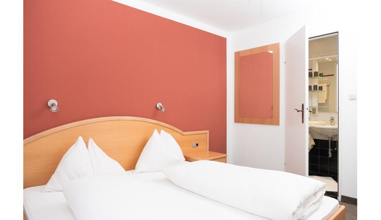 Doppelbett, Blick durch eine offene Tür ins Badezimmer