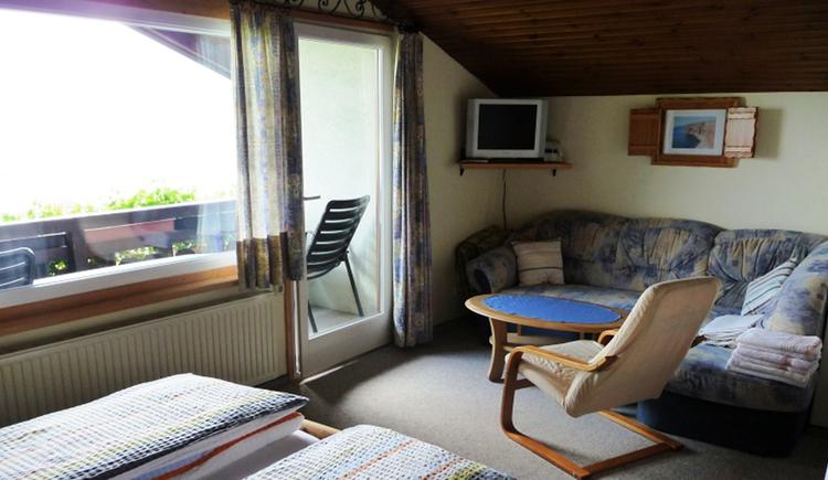 Schlaf-/Wohnbereich mit Doppelbett, großes Fenster, Balkontür, im Hintergrund Couch mit Tisch und Stuhl