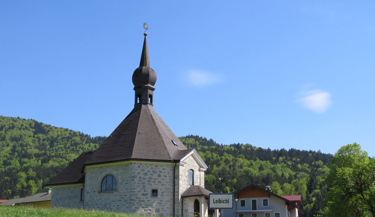 Blick auf eine Kirche, im Hintergrund ein Wald