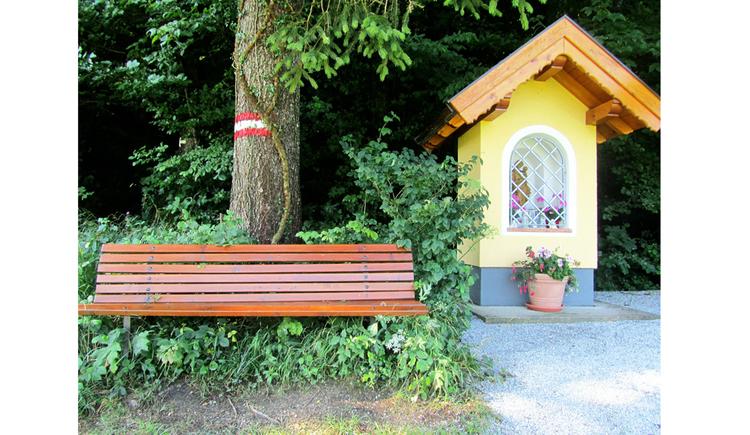 seitlich befindet sich eine kleine Kapelle, im Vordergrund eine Holzbank, Bäume
