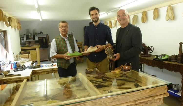 Der Goiserer Schuhmacher Philipp Schwarz steht mit Bürgermeister Peter Ellmer und Vizebürgermeister Helmut Pilz in der Werkstatt und hält einen Goiserer Schuh. (© Gemeinde Bad Goisern)