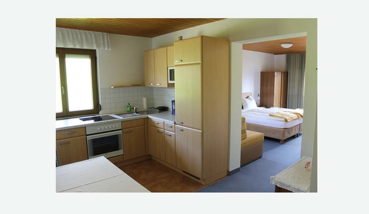 Kitchen with stove, microwave, coffee machine, small view of the bedroom with double bed and wardrobe