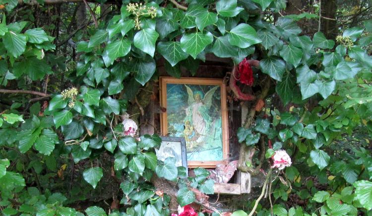 Blick auf ein Schutzengelbild umgeben von Blätter