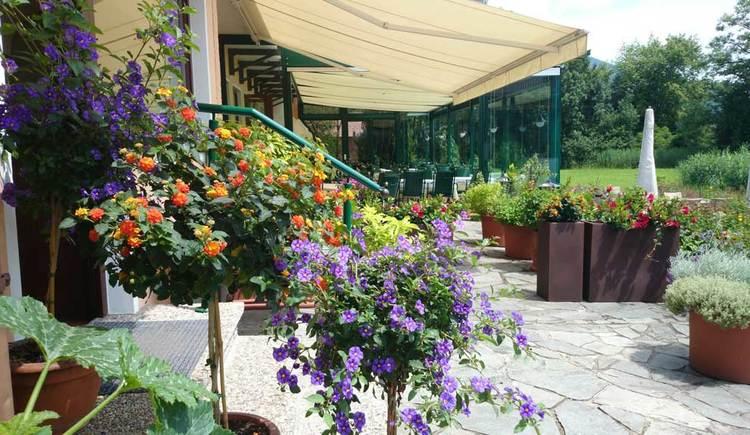 Garten mit Tischen und Stühlen, im Vordergrund einige Pflanzen. (© Seehotel Lackner)