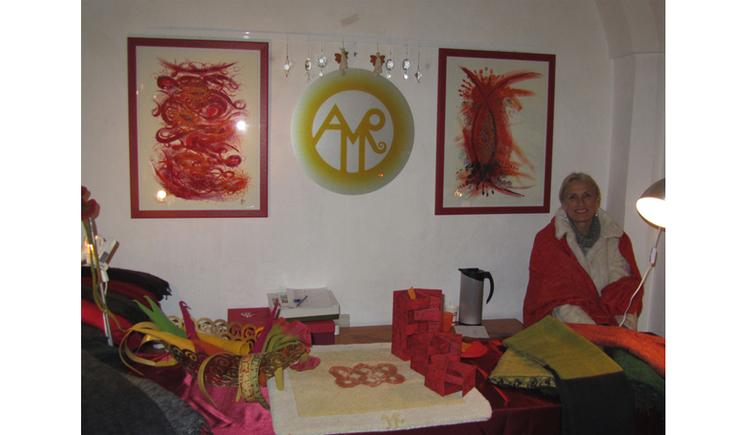Person sitzt im Hintergrund, an der Wand hängen Bilder, im Vordergrund auf einem Tisch gefilzte Gegenstände