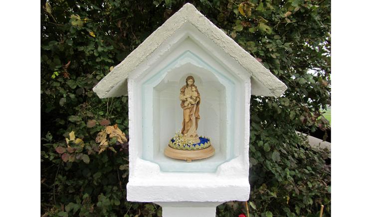Blick auf ein Marterl mit einer Heiligenfigur, im Hintergrund Bäume