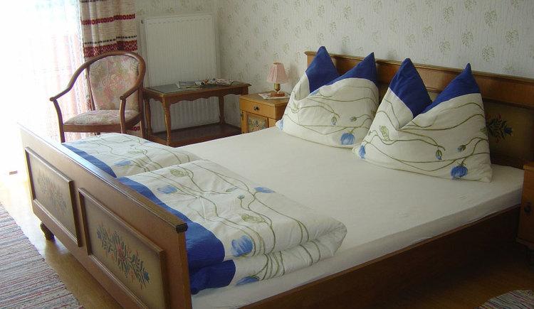 Schlafzimmer mit Doppelbett, Nachtkästchen mit Tischlampe, im Hintergrund ein kleiner Tisch mit Stuhl, Balkontür