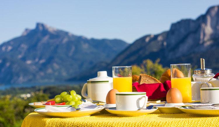 gedeckter Frühstückstisch im freien mit Eier, Weintrauben, Tomaten, Semmel und Brot, im Hintergrund verschwommen zu sehen der See und die Berge