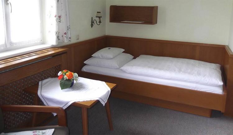 Schlafzimmer mit Einzelbett, seitlich ein Fenster und ein Tisch, Teppichboden